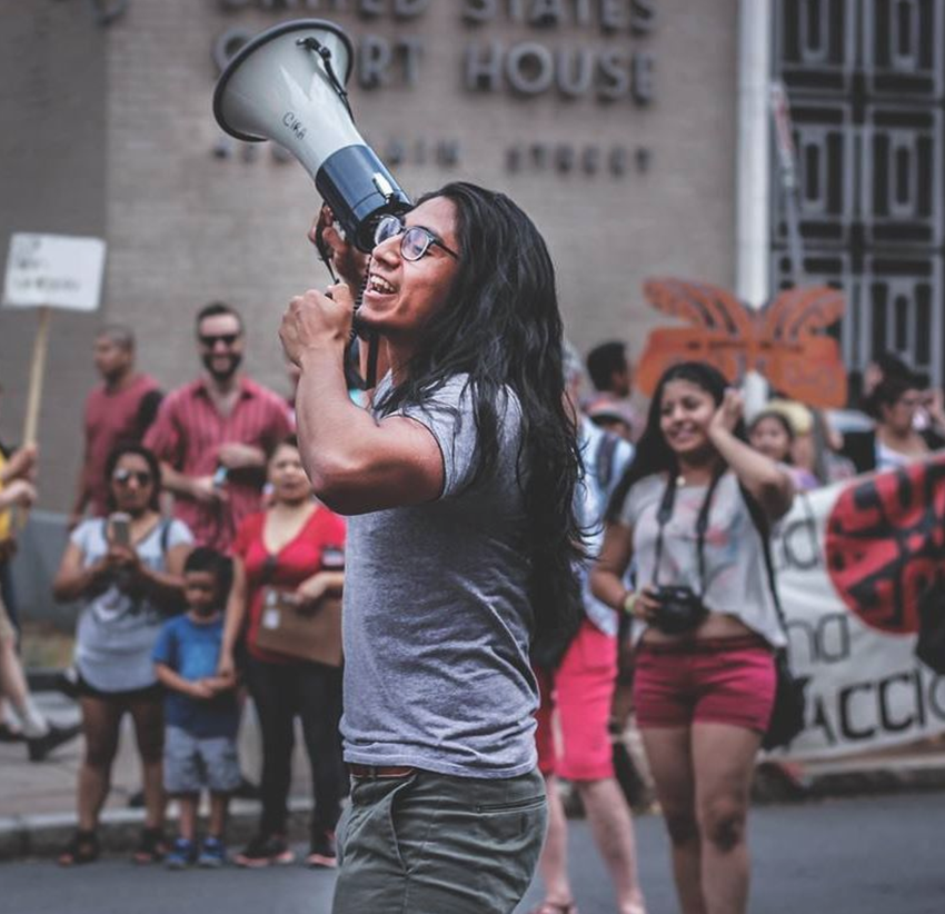 Photo of Eric holding a megaphone at a rally with other activists.