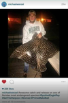 Photo of Wenzel holding a       spotted eagle ray      he illegally killed which is a protected species